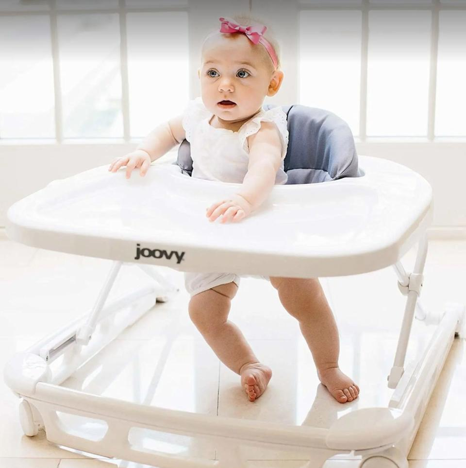 """This all-in-one walker will let your tiny kiddo snack, play and explore with ease. It also has a supportive seat pad that's machine-washable — which is great, because it <i>will</i> get messy.<br /><br /><strong>Promising review:</strong>""""My fiancé and I absolutely love this thing! We decided to spend a little bit of extra money and buy the Joovy walker over the other walkers on the market mostly because we didn't want to have to look at a pea green/pink walker all day (who makes these eyesores?), and we are so glad we did. This thing is very high quality! My favorite features about this is that the tray has a plastic cover on it so when you want to clean you just pop off the cover and wash in the sink, then replace. I also love how you push a latch down on the under side of the tray and you can fold the walker and store it in the corner.<strong>This walker has three adjustable heights and I was able to put my daughter in it when she was only 5 months old!</strong>The wheels also move freely and easily so you will have no problem with your baby being able to walk it around so long as you have tile flooring (I have no experience on low carpet)."""" —<a href=""""https://amzn.to/3hmg3HN"""" target=""""_blank"""" rel=""""nofollow noopener noreferrer"""" data-skimlinks-tracking=""""5189597"""" data-vars-affiliate=""""Amazon"""" data-vars-href=""""https://www.amazon.com/gp/customer-reviews/R6B6GUZQPUSHJ?tag=bfheather-20&ascsubtag=5189597%2C3%2C44%2Cmobile_web%2C0%2C0%2C160742"""" data-vars-keywords=""""cleaning"""" data-vars-link-id=""""160742"""" data-vars-price="""""""" data-vars-product-id=""""15996783"""" data-vars-retailers=""""Amazon"""">Jonathon Spencer<br /><br /></a><a href=""""https://amzn.to/3biy0mI"""" target=""""_blank"""" rel=""""noopener noreferrer""""><strong>Get it from Amazon for$99.99(available in four colors).</strong></a>"""
