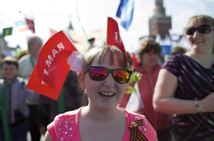 A girl and her mother smile as they march with members of Russian Trade Unions during the May Day celebration in Red Square, Moscow, Russia, on Thursday, May 1, 2014. About 100,000 people have marched through Red Square to celebrate May Day, the first time the annual parade has been held on the vast cobblestoned square outside the Kremlin since the fall of the Soviet Union in 1991. (AP Photo/Ivan Sekretarev)