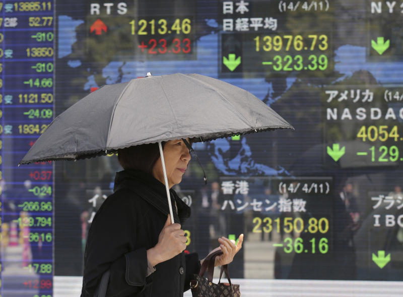 A woman walks by an electronic stock board of a securities firm in Tokyo, Friday, April 11, 2014. Tokyo's Nikkei 225 stock average fell more than 400 points at one point in morning trading. (AP Photo/Koji Sasahara)