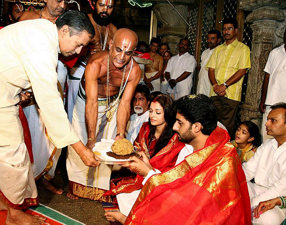 "Indian actors Abhishek Bachchan (2R) and Aishwarya Rai (C/R) are watched by Amitabh Bachchan (C) and industrialist Anil Ambani (R) as they take prasad (blessed food) from priests during a visit to The Lord Venkatesh Wara Temple at Tirupati,some 550 kms south of Hyderabad,22 April 2007. Bollywood stars Aishwarya Rai and Abhishek Bachchan began life as ""Mr and Mrs Bachchan"" 21 April, after three days of wedding celebrations for Indian cinema's ultimate power couple. AFP PHOTO/NOAH SEELAM"