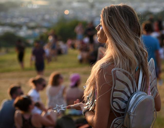 <p>Festival goers watch the sun set at the Glastonbury Festival of Music and Performing Arts on Worthy Farm near the village of Pilton in Somerset, South West England, on June 21, 2017. (Photo: Oli Scarff/AFP/Getty Images) </p>