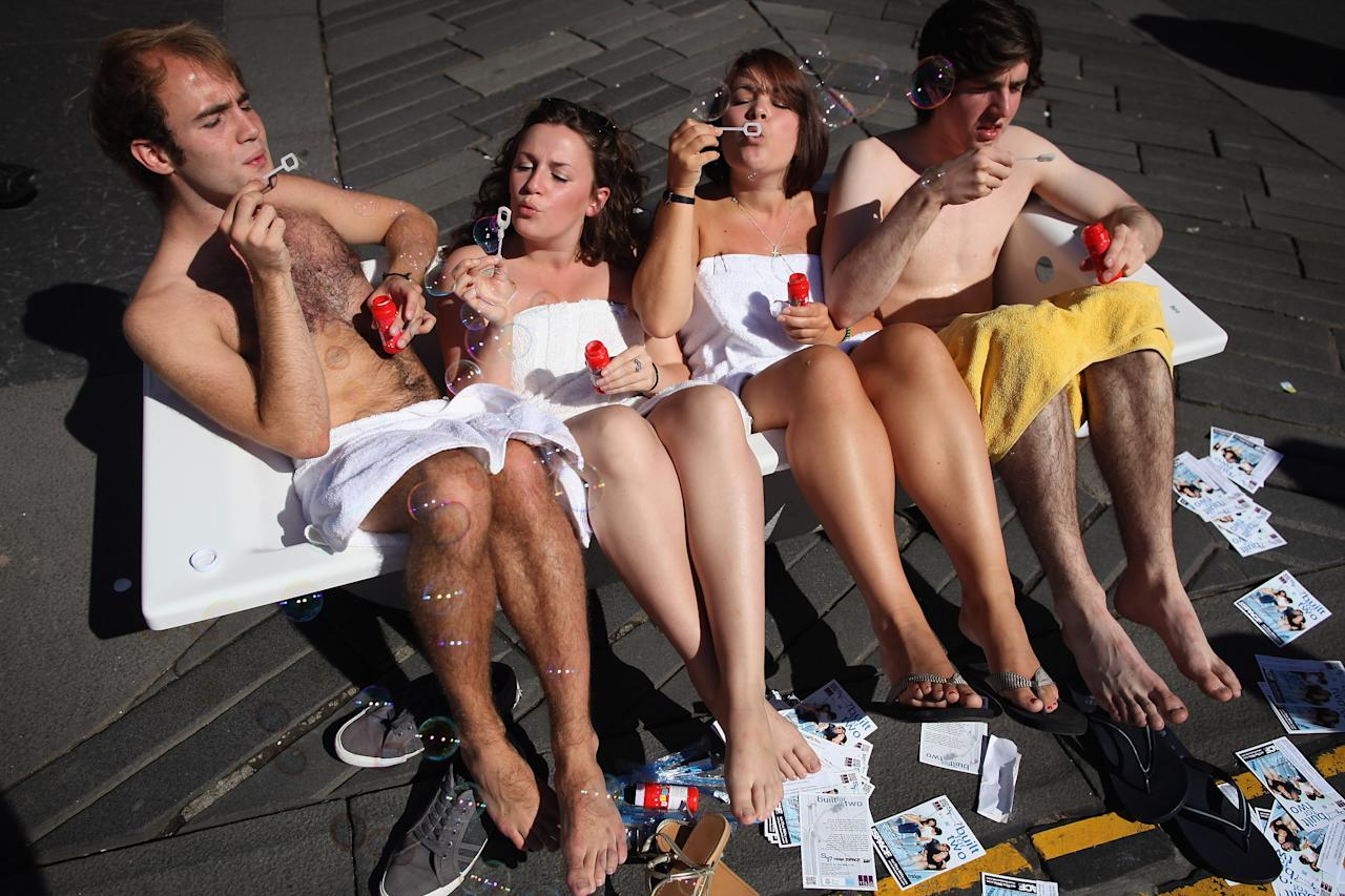 Street entertainers sit in a bath tub and blow bubbles as they perform on the Royal Mile to promote their shows during in the Edinburgh Fringe Festival on August 7, 2012 in Edinburgh, Scotland. (Photo by Dan Kitwood/Getty Images)