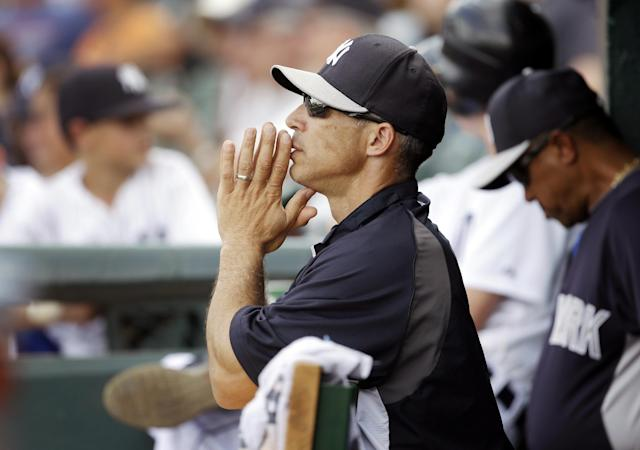 FILE - In this March 23, 2013, file photo, New York Yankees manager Joe Girardi stands in the dugout during an exhibition spring training baseball game against the Detroit Tigers in Lakeland, Fla. Girardi signed a four-year contract extension to stay with the New York Yankees, Wednesday, Oct. 9, 2013. (AP Photo/Carlos Osorio, File)