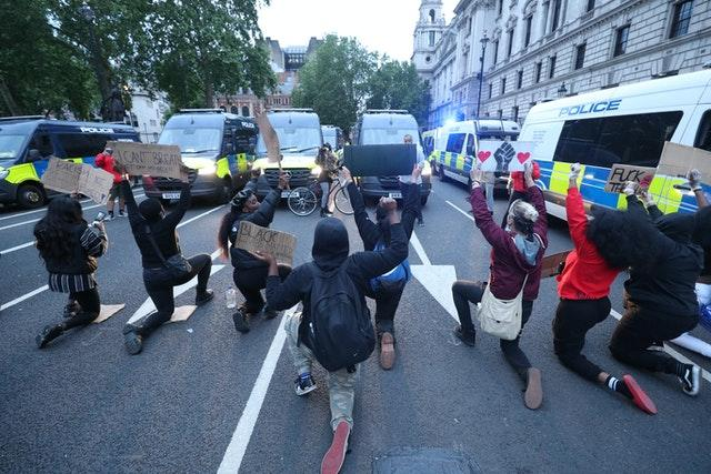 Protesters take a knee in front of police vans during a Black Lives Matter protest rally in Parliament Square