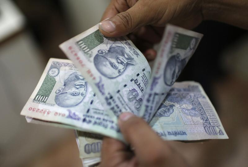 An employee counts Indian currency notes inside a private money exchange office in New Delhi