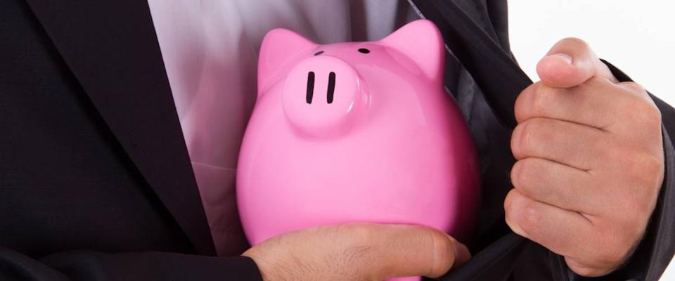 Pink piggy bank in safe with businessman in suit, isolated on white background.