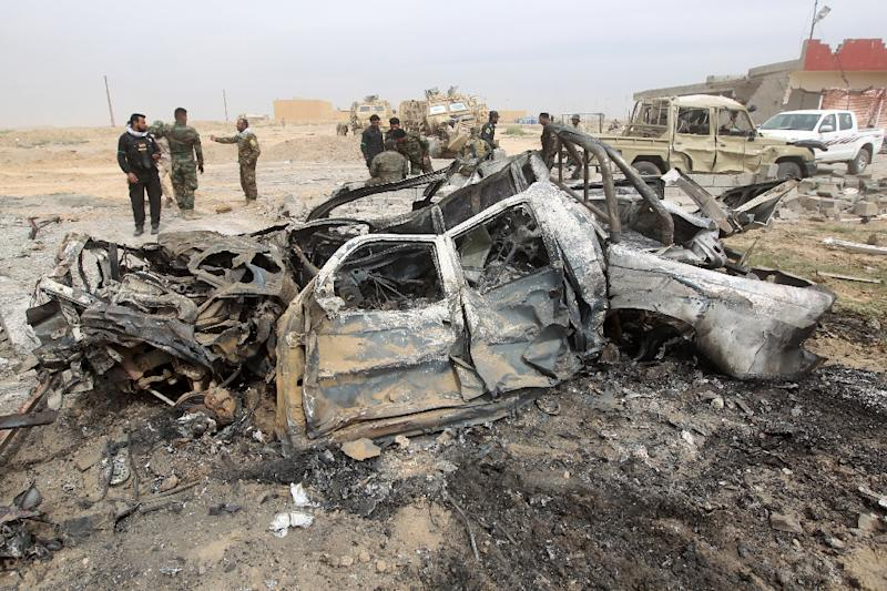 Iraqi Shiite fighters stand at the site of a car bomb on March 12, 2015 in a suburb of Tikrit during a military operation to retake the city from the Islamic state group (AFP Photo/Ahmad Al-Rubaye)
