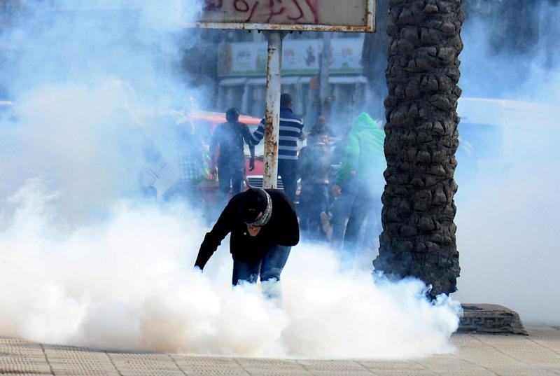 A protester is enveloped in tear gas fired by riot police to disperse a demonstration in Alexandria, Egypt, Monday, Dec. 2, 2013. Black clad riot police fired tear and chased dozens of rights activists and protesters who held a demonstration in the Mediterranean city demanding abolishing a new law that extensively restricted the right to hold a protest, imposing fines and jail terms on violators.(AP Photo/Heba Khamis)