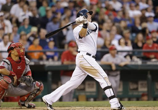 Seattle Mariners' Justin Smoak hits a three-run home run as Los Angeles Angels catcher Hank Conger watches in the sixth inning of a baseball game Saturday, July 13, 2013, in Seattle. (AP Photo/Elaine Thompson)