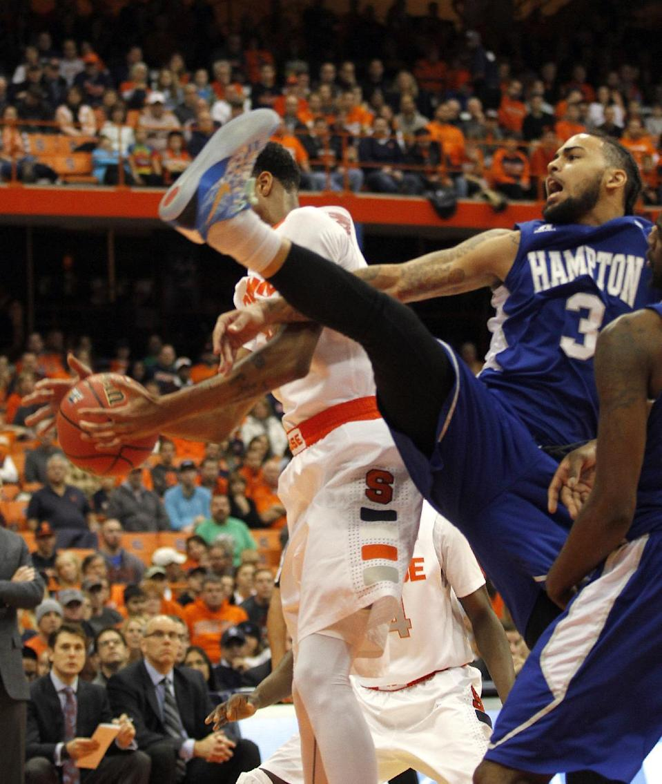 Hampton's Quinton Chievous, right, falls as he battles for a rebound against Syracuse's Chris McCullough, left, in the first half of an NCAA college basketball game in Syracuse, N.Y., Sunday, Nov. 16, 2014. (AP Photo/Nick Lisi)