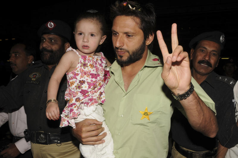 Shahid Afridi, captain of Pakistani Cricket team flashes a victory sign holding his daughter at Karachi airport on Monday night Feb. 7, 2011. The team  arrived in  Pakistan after beating New Zealand. (AP Photo/Jamal Ahmed)
