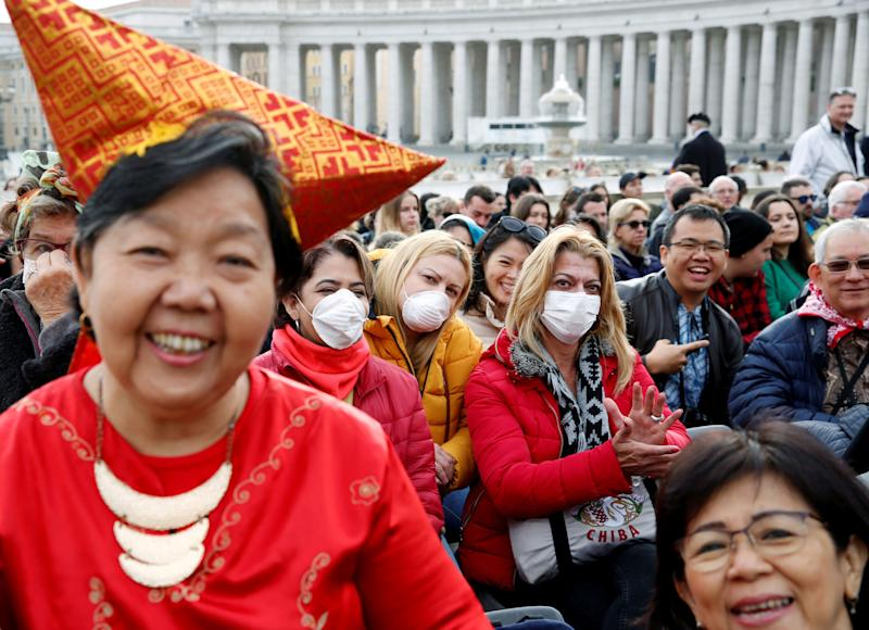 People, a few in face masks, wait for Pope Francis to arrive for his weekly general audience at the Vatican. (Photo: Remo Casilli / Reuters)