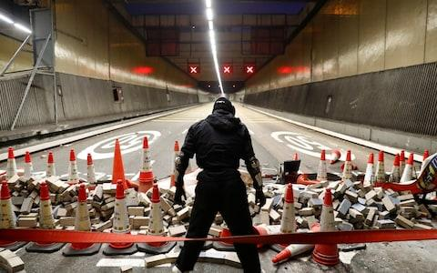 An anti-government protesters stands at a blocked outlet of the Cross Harbour Tunnel near the Polytechnic University in Hong Kong - Credit: Reuters