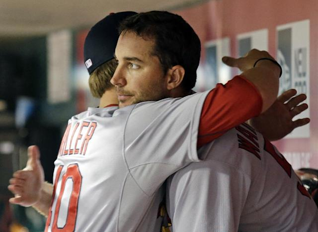 St. Louis Cardinals starting pitcher Adam Wainwright is hugged by Shelby Miller, left, after Wainwright was taken out at the end of the eighth inning of a baseball game against the Cincinnati Reds, Sunday, May 25, 2014, in Cincinnati. Wainwright earned the win with eighth shutout innings and 12 strikeouts. St. Louis won 4-0. (AP Photo/Al Behrman)