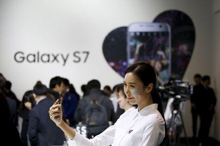 File photo of a model posing for photographs with Samsung Electronics' new smartphone Galaxy S7 during its launching ceremony in Seoul