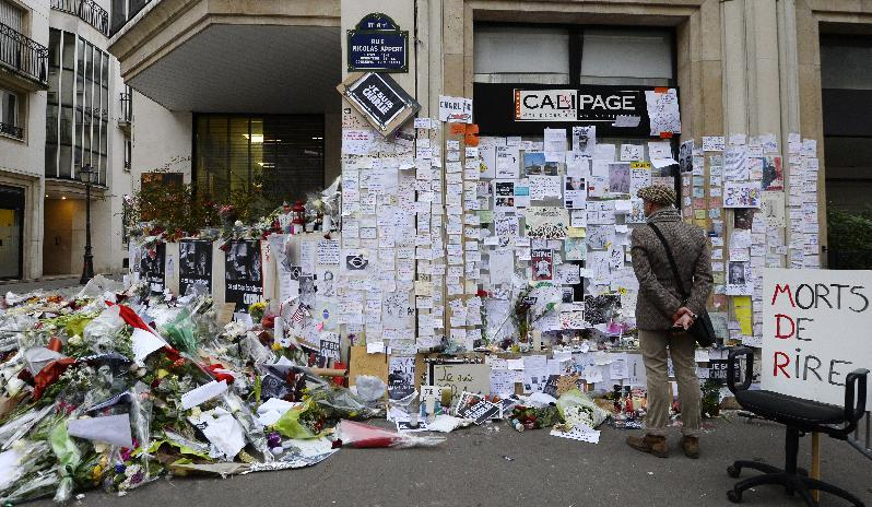 People visit a makeshift memorial near the headquarters of French satirical weekly Charlie Hebdo on January 12, 2015 in Paris, France
