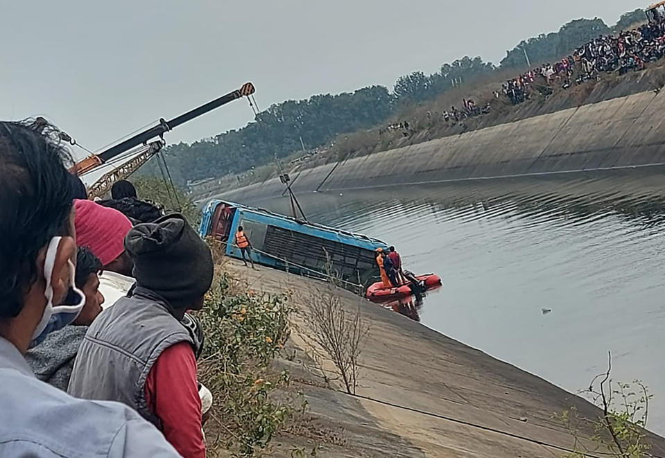 A bus that fell into a canal is pulled out in Sidhi district, in the central Indian state of Madhya Pradesh, Tuesday, Feb. 16, 2021. An official says an overcrowded bus has driven off a bridge and into a canal in central India, killing at least 40 people. (Madhya Pradesh District Public Relation Office Sidhi via AP)