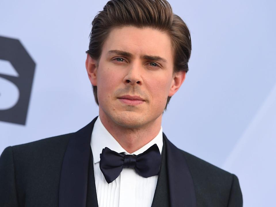 Actor Chris Lowell wearing a black suit and matching bow-tie at the 2019 Screen Actors Guild Awards in Los Angeles.