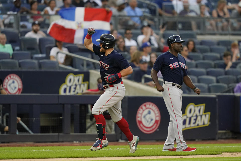 Boston Red Sox third base coach Carlos Febles, right, looks on as Christian Arroyo runs the bases after hitting a two-run home run during the second inning of a baseball game against the New York Yankees, Friday, July 16, 2021, in New York. (AP Photo/Frank Franklin II)