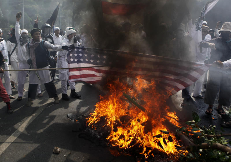 "Muslim protesters burn a U.S. flag during a protest against American-made film ""Innocence of Muslims"" that ridicules Islam and depicts the Prophet Muhammad as a fraud, a womanizer and a madman, outside the U.S. Embassy in Jakarta, Indonesia, Monday, Sept. 17, 2012. (AP Photo/Dita Alangkara)"