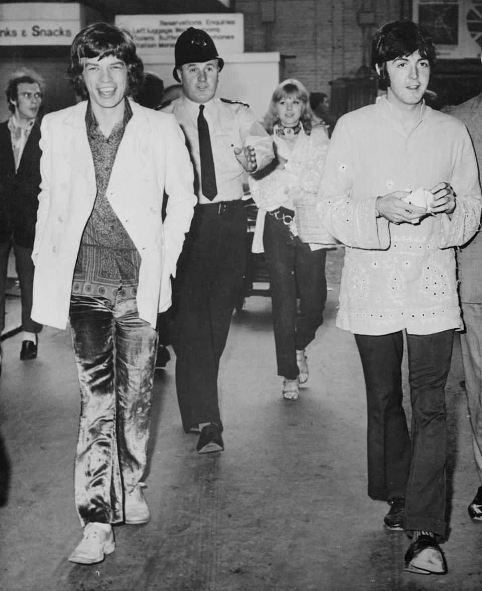 """(Original Caption) All aboard the """"love"""" train...Beatle Paul McCartney, wearing an Indian-style jacket, and Mick Jagger (left) of the Rolling Stones, walk toward train en route to a love pilgrimage to Bangor. The Beatles and Jagger are to hear the Himalayan mystic Maharishi Yogi give a series of meditation lectures."""