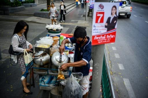A vendor attends to a customer next to an electoral poster in Bangkok ahead of the March 24 general election