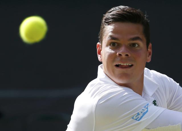 Milos Raonic of Canada hits a return during his men's singles semi-final tennis match against Roger Federer of Switzerland at the Wimbledon Tennis Championships, in London July 4, 2014. REUTERS/Stefan Wermuth (BRITAIN - Tags: SPORT TENNIS)