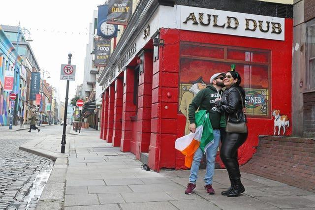 Anderson Lima and Julianna Santos, originally from Brazil but living in Ireland, celebrate St Patrick's Day on a quiet Temple Street in Dublin (Brian Lawless/PA)