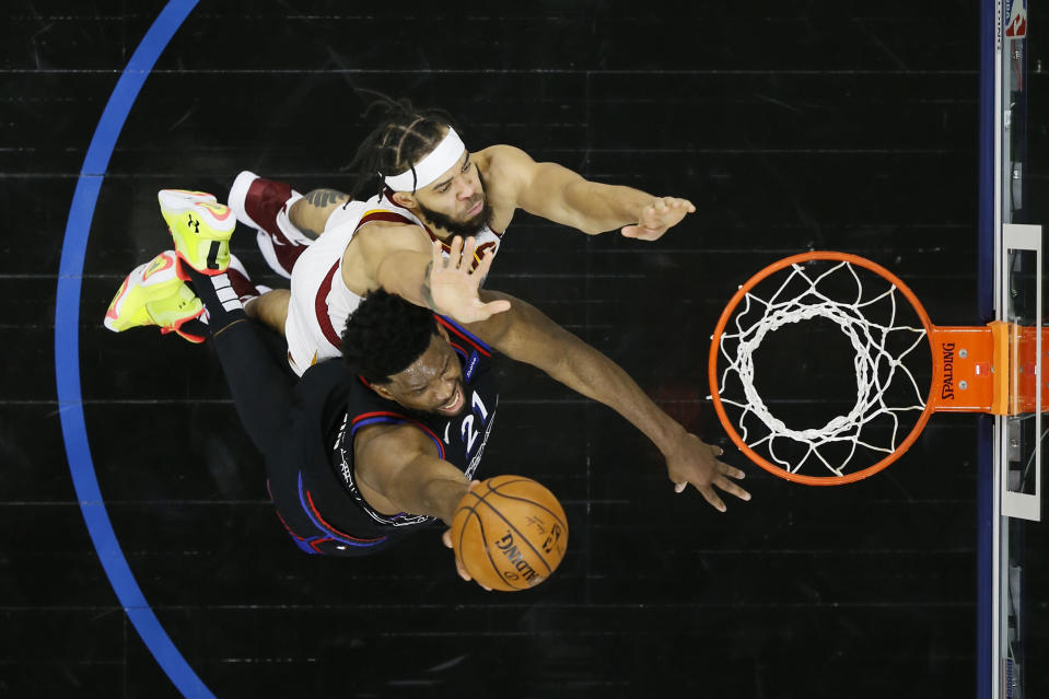 Philadelphia 76ers' Joel Embiid, bottom, goes up for a shot against Cleveland Cavaliers' JaVale McGee during the first half of an NBA basketball game, Saturday, Feb. 27, 2021, in Philadelphia. (AP Photo/Matt Slocum)