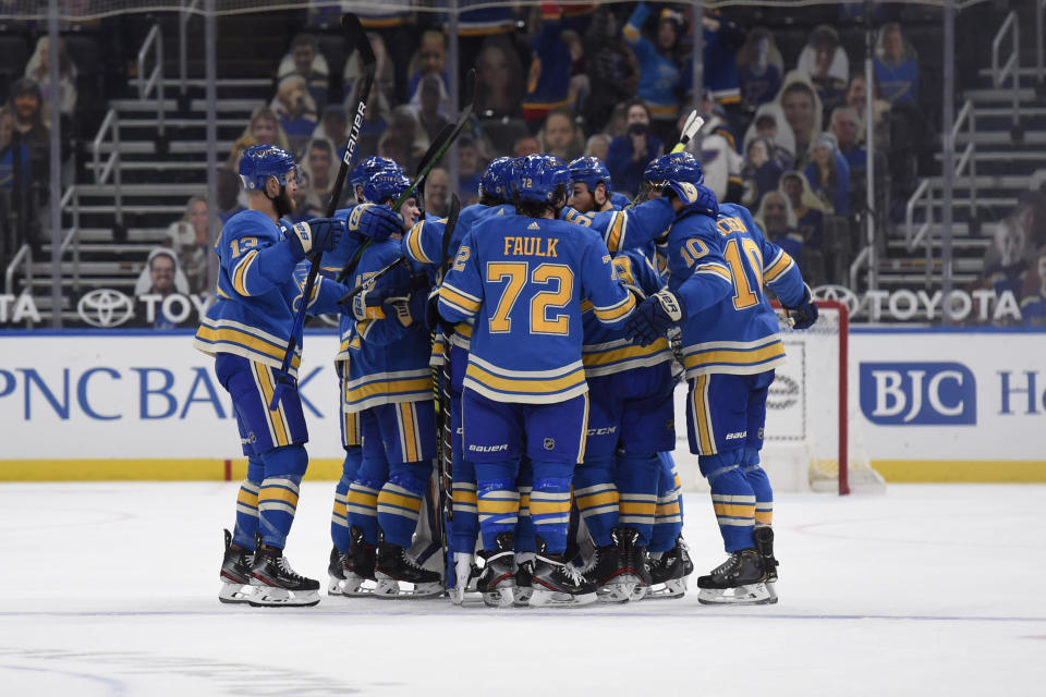 St. Louis Blues' Ryan O'Reilly (90) is congratulated by teammates after scoring the winning goal against the Minnesota Wild during overtime of an NHL hockey game on Saturday, April 10, 2021, in St. Louis. (AP Photo/Joe Puetz)