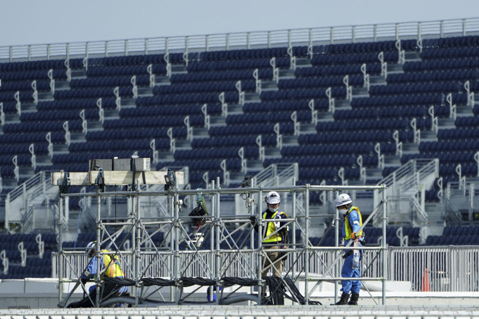 Workers prepare the venue at Kasai Canoe Slalom Centre for the Tokyo 2020 Olympics Thursday, April 8, 2021, in Tokyo. Many preparations are still up in the air as organizers try to figure out how to hold the postponed games in the middle of a pandemic. (AP Photo/Eugene Hoshiko)