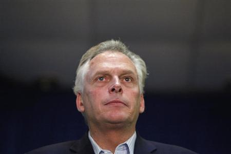 McAuliffe stands onstage as Clinton campaigns for him at an event in Dale City, Virginia
