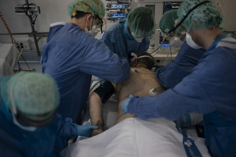 Healthcare workers assist a COVID-19 patient at a library that was turned into an intensive care unit (ICU) at Germans Trias i Pujol hospital in Badalona, Barcelona province, Spain, April 1, 2020. (AP Photo/Felipe Dana)