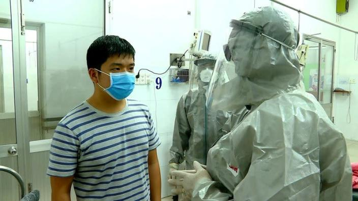 Vietnam's Vice Minister of Health Nguyen Truong Son talks with a man at an isolated section of a hospital where two Chinese citizens had tested positive for coronavirus, in Ho Chi Minh city