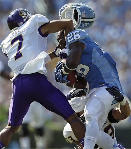 East Carolina's Lamar Ivey (7) and Jeremy Grove, bottom, hit North Carolina's Giovani Bernard (26) during the first half of an NCAA college football game in Chapel Hill, N.C., Saturday, Sept. 22, 2012. (AP Photo/Gerry Broome)