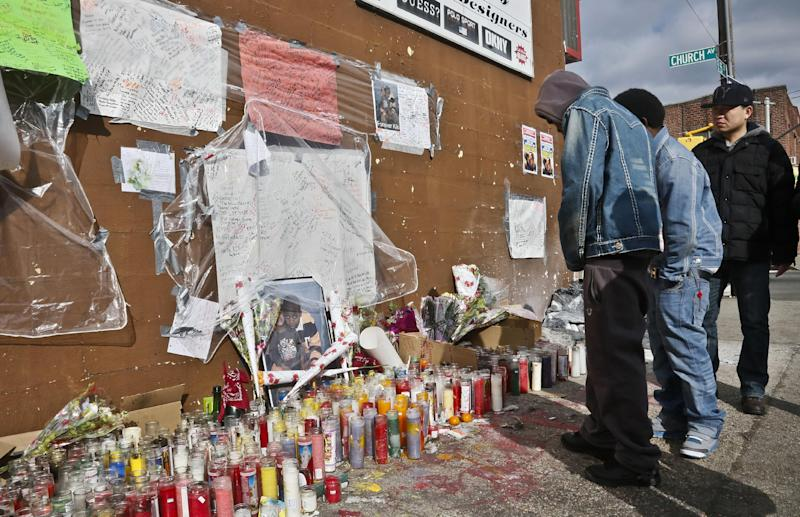 """People visit a growing makeshift memorial for police shooting victim Kimani """"Kiki"""" Gray on Thursday, March 14, 2013 in the East Flatbush neighborhood of Brooklyn, N.Y.  The 16-year-old was shot to death on a Brooklyn street last Saturday night by plainclothes police officers. (AP Photo/Bebeto Matthews)"""