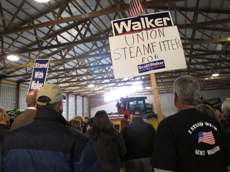 Retired union steamfitter Mike Reynders of Fort Atkinson, right, holds a sign in support of Wisconsin Gov. Scott Walker while listening to Lt. Gov. Rebecca Kleefisch speak Tuesday, April 10, 2012, in Dane, Wis. Walker and Kleefisch spent the day campaigning around the state two months away from the June 5 recall election. (AP Photo/Scott Bauer)