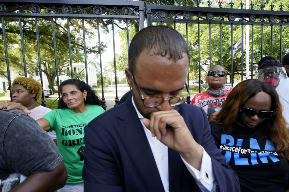Mona Hardin, background left in green, mother of Ronald Greene, prays outside the gates of the governor's mansion in Baton Rouge, La., Thursday, May 27, 2021, protesting the death of Greene, who died in the custody of Louisiana State Police in 2019. Foreground is Ron Haley, attorney for the Greene family. (AP Photo/Gerald Herbert)