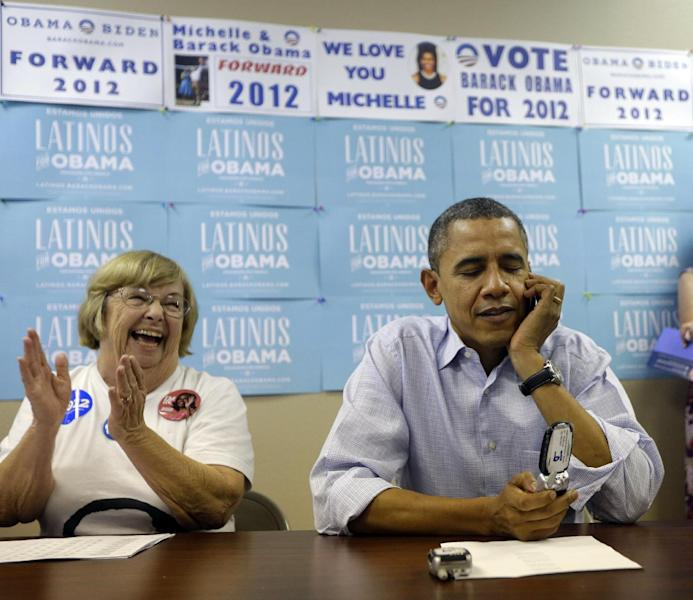 President Barack Obama, right, calls supporters as campaign worker Ellen Merill, left, reacts at a local campaign office, Monday, Oct. 1, 2012 in Henderson, Nev. (AP Photo/Pablo Martinez Monsivais)