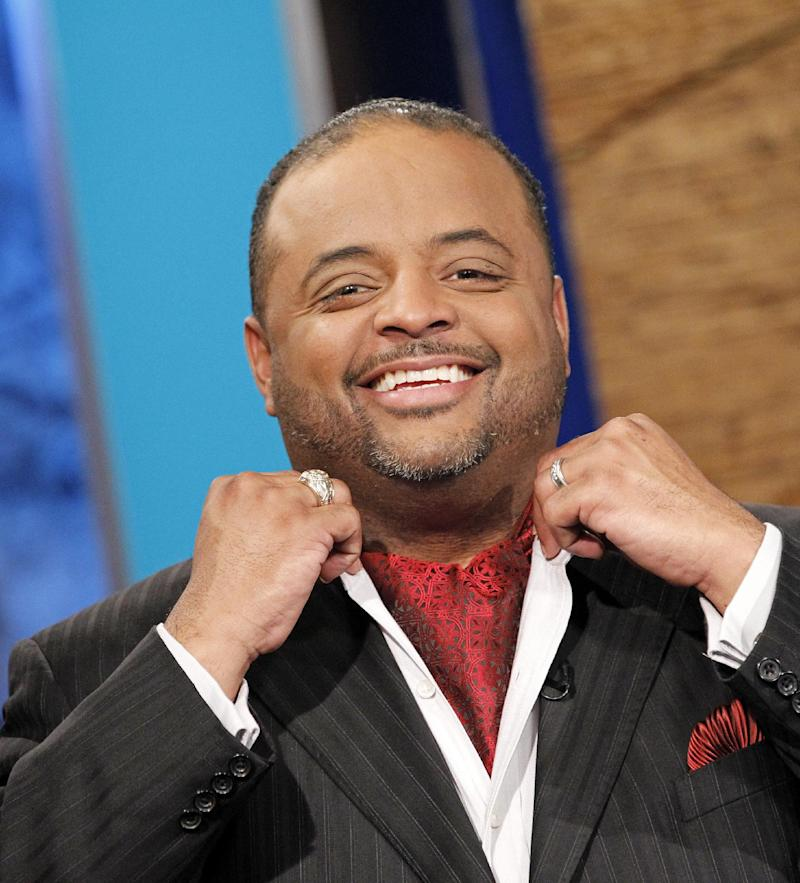 "FILE -- In a May 14, 2010 photo Roland Martin, wearing an ascot, adjusts his collar before a news segment in Washington.  CNN suspended political analyst Martin on Wednesday Feb. 8, 2012 for ""offensive"" tweets during the Super Bowl (AP Photo/Haraz N. Ghanbari, file)"