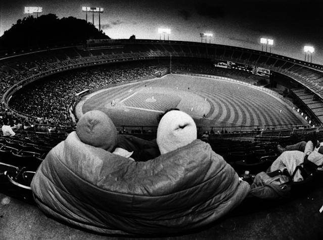 FILE - In this July 9, 1985, file photo, two women take shelter from the cold with a sleeping bag on the upper deck of Candlestick Park in San Francisco. Candlestick Park, known for its bone-numbing winds, the Catch and the earthquake-rocked 1989 World Series is officially closing after more than a half century of hosting sporting and cultural events. In a bow to historical symmetry, the Stick's finale will be a performance Thursday by Paul McCartney, 48 years after the Beatles' last scheduled concert lit up the venue. (AP Photo/Eric Risberg, File)