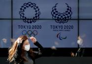FILE PHOTO: A passerby wearing a protective face mask following the coronavirus outbreak walks past a screen displaying logos of Tokyo 2020 Olympic and Paralympic Games in Tokyo