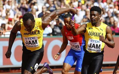 Athletics - World Athletics Championships - Men's 4x100 Metres Relay Heats - London Stadium, London, Britain – August 12, 2017. Usain Bolt and Micheal Campbell of Jamaica in action. REUTERS/Kai Pfaffenbach