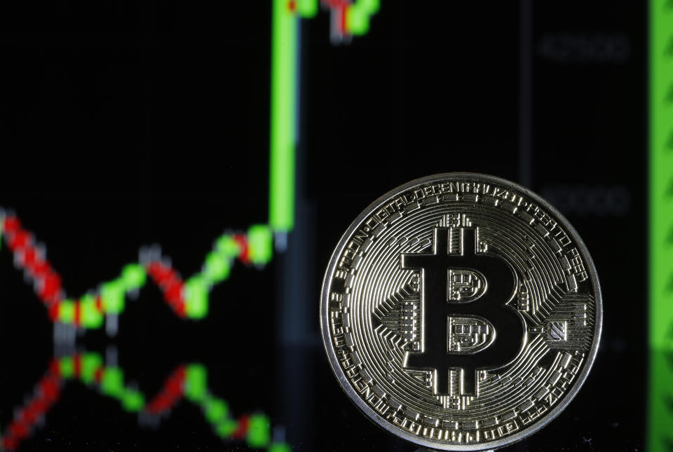 PARIS, FRANCE - FEBRUARY 09: In this photo illustration, a visual representation of the digital Cryptocurrency, Bitcoin is on display in front of the Bitcoin course's graph on February 09, 2021 in Paris, France. The value of Bitcoin (BTC) has exceeded the threshold of 48,000 dollars for the first time in history. Electric vehicle maker Tesla has invested $ 1.5 billion in the virtual currency and will begin accepting it as payment for the purchase of its cars, the group said. The move comes days after Elon Musk temporarily changed his Twitter mini-description to simply #bitcoin.  (Photo illustration by Chesnot/Getty Images)