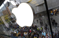 FILE - In this Friday, Sept. 25, 2015, file photo, people wait in front of an Apple store in Munich, before the worldwide launch of the iPhone 6s. A European Union high court on Wednesday, July 15, 2020 ruled in favor of technology giant Apple and Ireland in its dispute with the EU over 13 billion euros, 15 billion US dollars in back taxes. (AP Photo/Matthias Schrader, File)