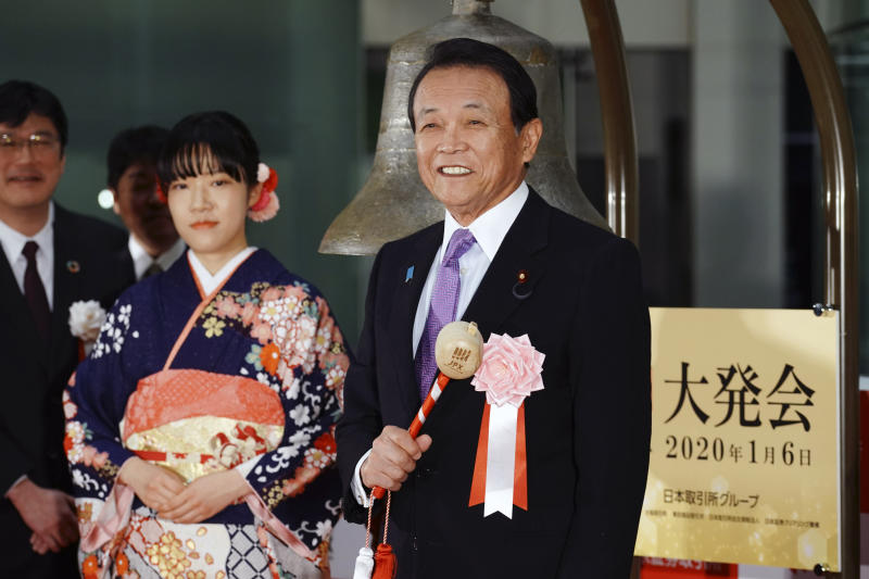 Japan's Finance Minister Taro Aso, right, poses before tolling a bell during a ceremony marking the start of this year's trading in Tokyo Monday, Jan. 6, 2020, in Tokyo. (AP Photo/Eugene Hoshiko)