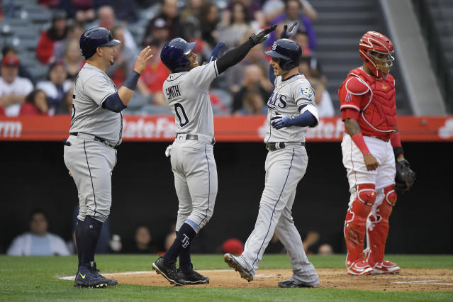 Tampa Bay Rays' Daniel Robertson, second from right, celebrates with Jesus Sucre, left, and Mallex Smith, second from left, as Los Angeles Angels catcher Martin Maldonado stands at the plate after hitting a grand slam during the second inning of a baseball game Saturday, May 19, 2018, in Anaheim, Calif. (AP Photo/Mark J. Terrill)