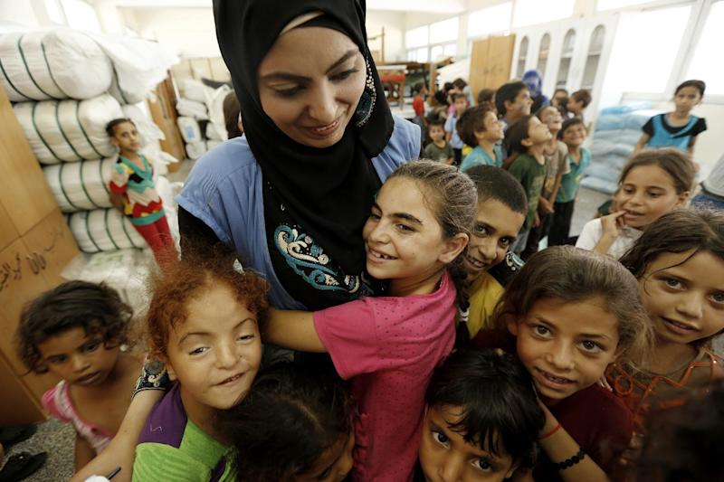 Palestinian children affected by the war gather around a UN volunteer at a school in Jabalia as part of a United Nations community mental health programmes in the Gaza Strip, on August 2, 2014 (AFP Photo/Mohammed Abed)