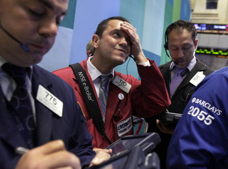 Trader Michael Zicchinolfi, center, works on the floor of the New York Stock Exchange Monday, Oct. 22, 2012. A weak forecast from heavy equipment maker Caterpillar and other poor earnings results weighed on the U.S. stock market in early trading. (AP Photo/Richard Drew)