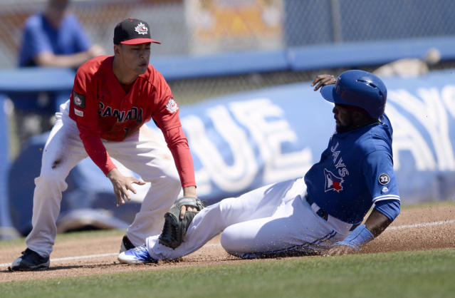 Canada Junior National Team third baseman TJ Schofield-Sam tags out Toronto Blue Jays Dwight Smith Jr. during the first inning of a spring training baseball game Saturday, March 17, 2018, in Dunedin, Fla. (AP Photo/Jason Behnken)